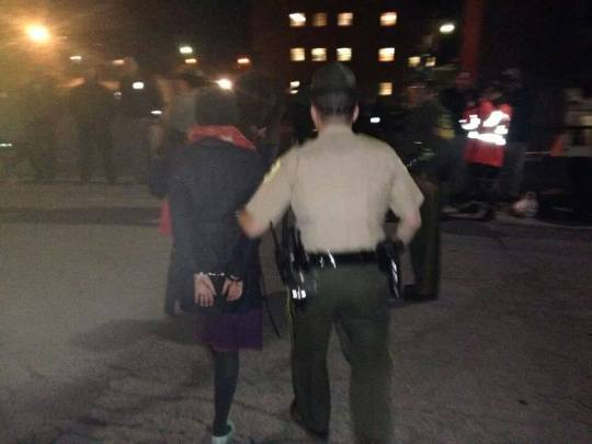 Maeve McBride, organizer for 350 Vermont and mother of two being led away from Governor Peter Shumlins office on Monday night.  63 other protestors were arrested with her.